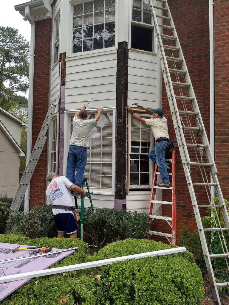 3 men repairing rotted wood on exterior home