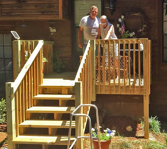 man and woman standing on new deck outside home