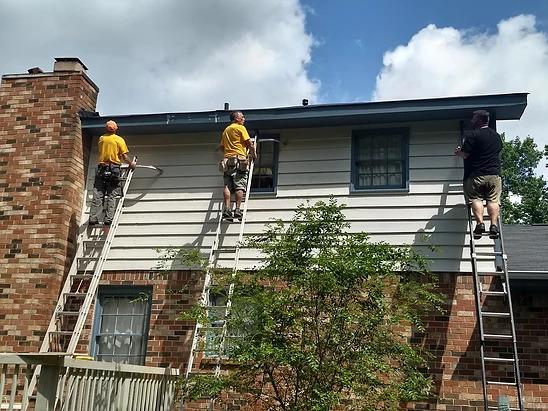 men on ladders repairing exterior of home