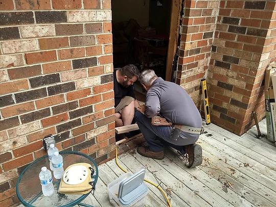 two men on floor repairing an entryway