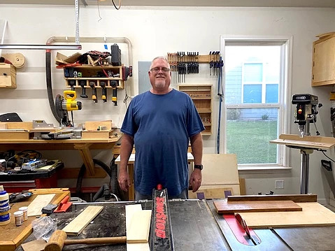 Jess standing in his workshop surrounded by tools