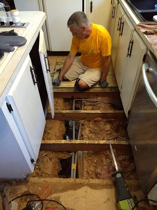 man on floor of kitchen with flooring being installed