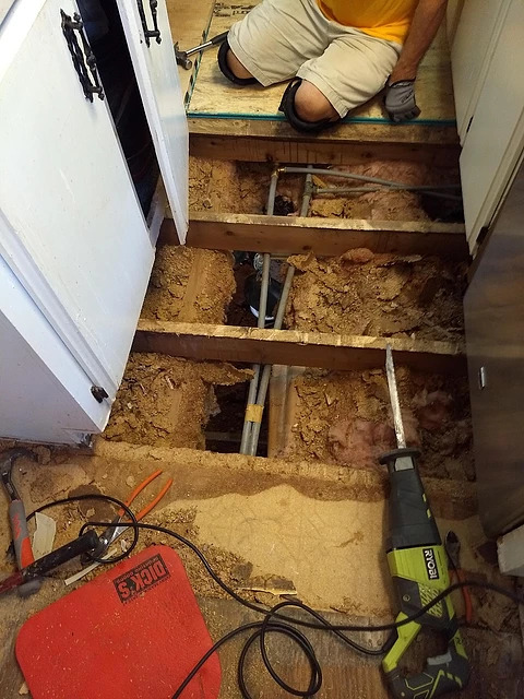 close up of kitchen with exposed holes and issues in fflooring