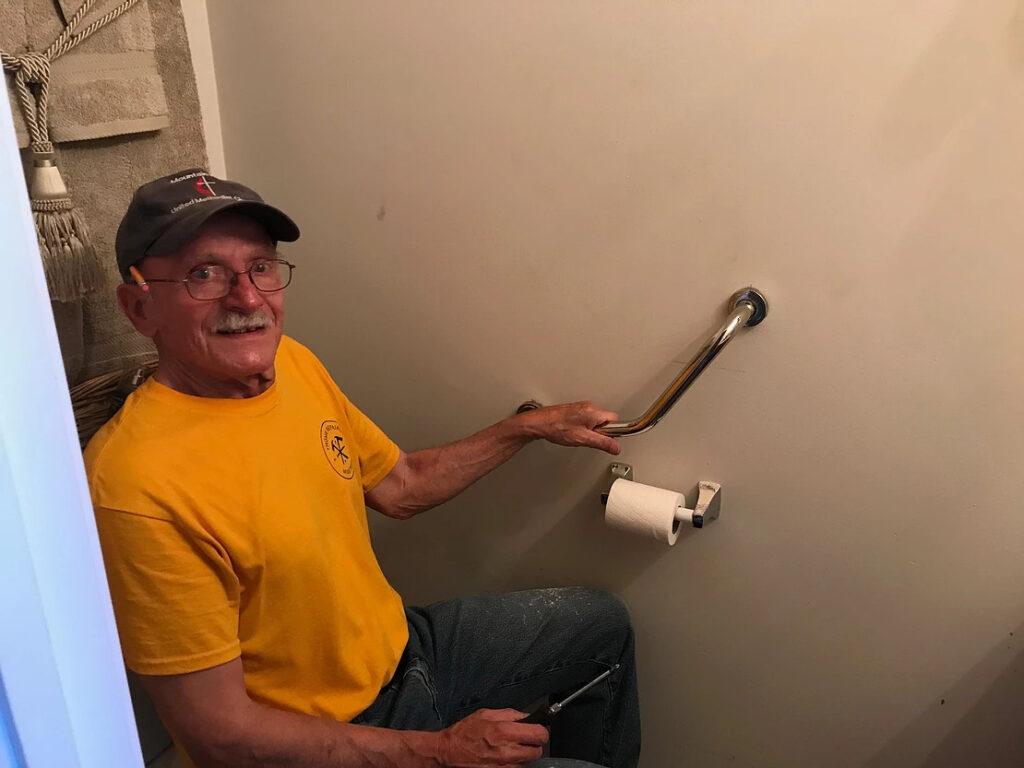 Man in yellow shirt installing handle bar near toilet