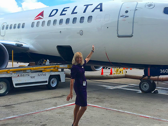 Sandy standing in front of Delta airplane