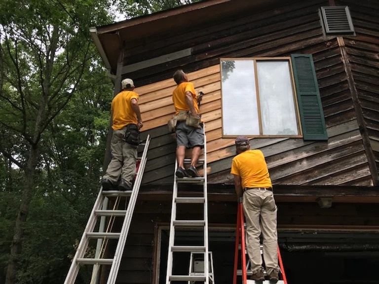 three men on ladders repairing exterior siding