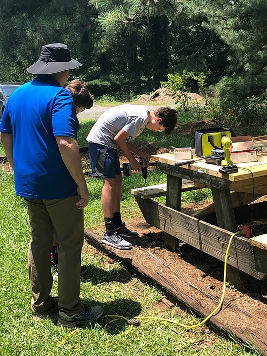 teens drilling wood pieces together outside