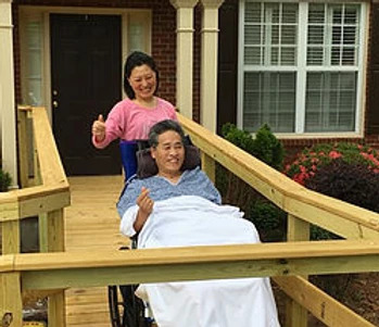 man in wheelchair smiling with wife on new accessible ramp