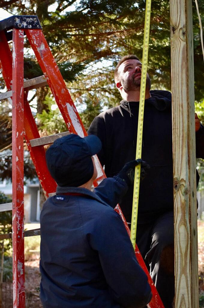 Two men measuring on ladders
