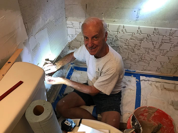 Man adding tile and grout