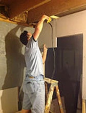 man on ladder finishing drywall with a drill