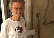 woman holding grip bar installed in the shower